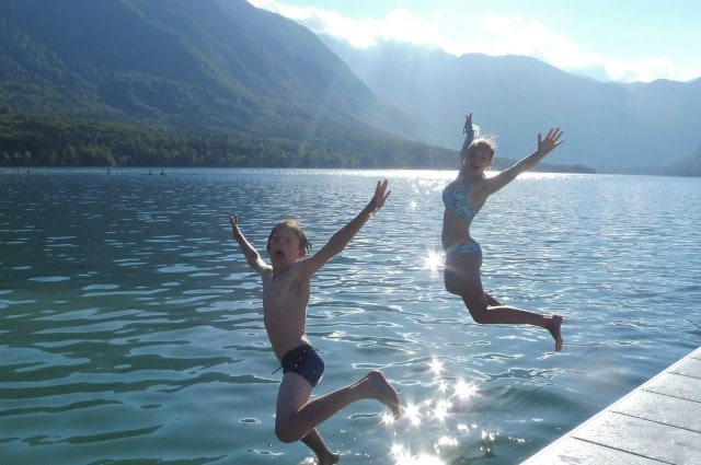 Children jumping into Lake Bohinj Slovenia