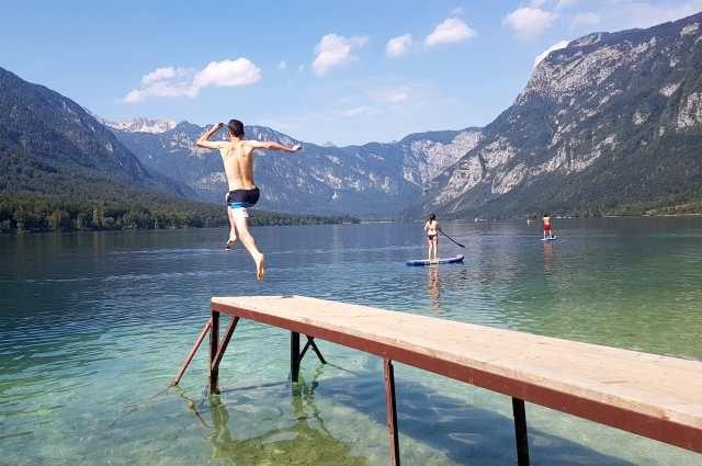 Jumping and swimming at Lake Bohinj in Slovenia